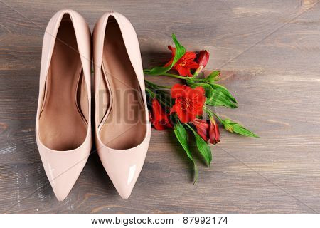 Female shoes with flowers on wooden background