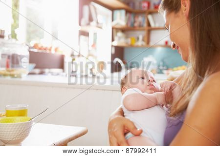 Mother Holding Newborn Baby Daughter At Kitchen Table