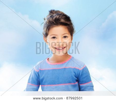childhood, people and happiness concept - little student girl over blue sky background