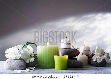 Beautiful composition with candles and spa stones on light background