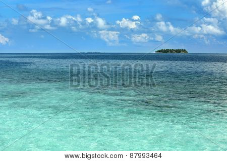 View of beautiful blue ocean water and island on horizon in Baros Maldives