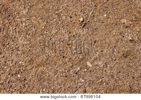 Red clay surface. Small stones. Abstraction. Background.
