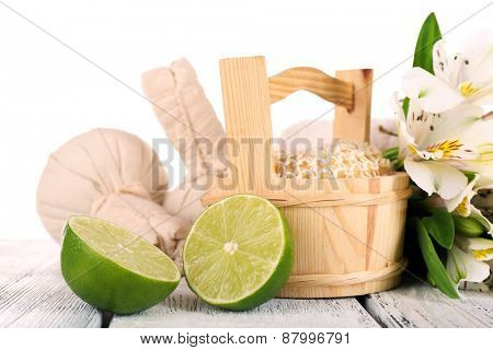 Spa still life with flower and lime on wooden table isolated on white