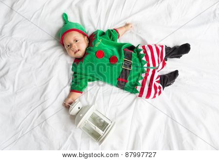 Baby in elf costume for christmas holiday on white background with a lantern