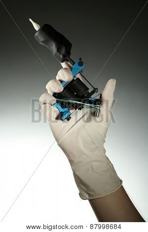 Tattoo artist holding tattoo machine, on colorful background