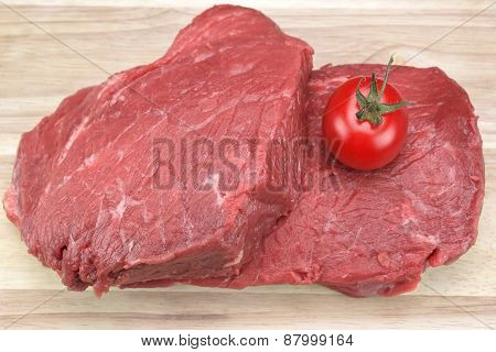One Raw Beef Steak And Tomato Close-up
