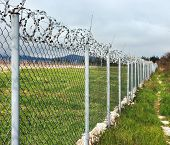 stock photo of barbed wire fence  - Concertina wire atop a fence protect in the nature - JPG