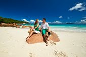 foto of couple sitting beach  - Couple in green sitting on a rock at tropical Seychelles beach - JPG