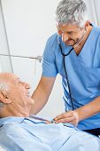 picture of male nurses  - Smiling male caretaker examining senior man with stethoscope in bedroom at nursing home - JPG