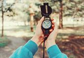 image of pov  - Traveler woman searching direction with a compass in summer forest - JPG