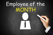 stock photo of employee month  - businessmans hand writing employee of the month on black chalkboard - JPG
