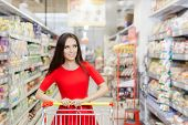 pic of local shop  - Portrait of a young girl in a market store with a shopping cart - JPG