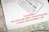 foto of restriction  - drug restriction notice for Singapore travelers over passport page with immigration stamp - JPG