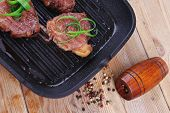 stock photo of bloody  - roast bloody beef fillet steaks on black teflon grill plate on wood - JPG
