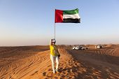 image of arabic woman  - Woman in the desert next to the flag of the United Arab Emirates - JPG