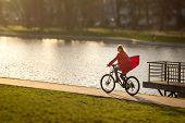 picture of tilt  - happy girl drives on bike near pond - JPG