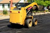 pic of skid-steer  - Small skid steer tractor moving asphalt on a repaving project - JPG