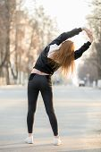 pic of stretching exercises  - Runner girl doing warming up exercises for spine before morning jogging on the street stretching preparing for running back view - JPG