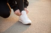 foto of jogger  - Female hands fixing laces on white sneakers in warm light on concrete jogger preparing for running practice close - JPG