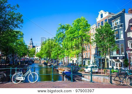 Beautiful canal and traditional bikes in old city of Amsterdam, Netherlands, North Holland province.