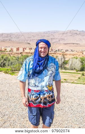 TINERHIR, MOROCCO, APRIL 11, 2015: Tourist poses for photo in berber blue turban with Tinerhir - town near Todgha Gorge in background