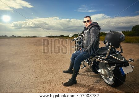 Biker in leather jacket sitting on a motorcycle.