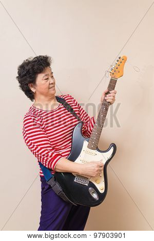 Portrait Of Adult Asian Woman With Electric Guitar On Reddish Yellow Gray Wall Background