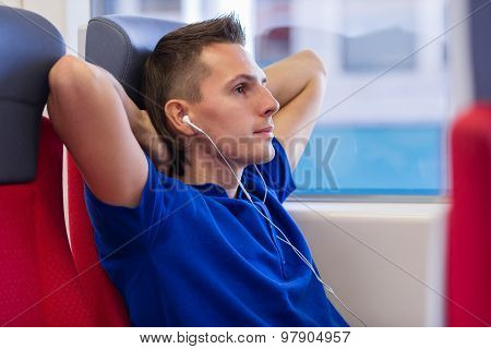 Young happy man listening music traveling by train
