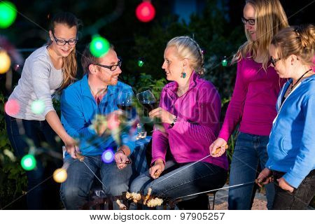 Family grilling bread on a stick at barbecue in garden at nighttime