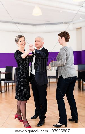 Dance instructor with senior couple of woman and man