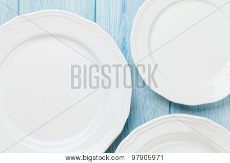 Empty plates over wooden table background. View from above with copy space