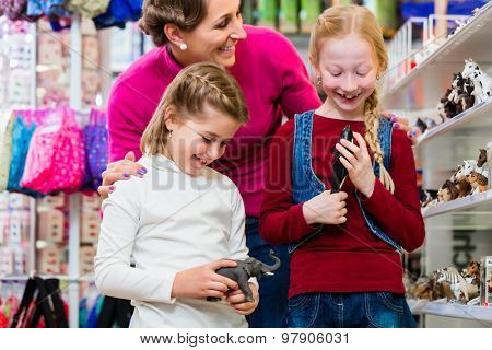 Family buying toys in toy store in toy store standing on a shelf choosing figures