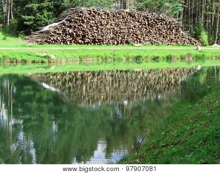 Pile of firewood in front of a small mountain lake . The woodpile is reflected on the lake