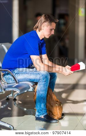 Young manwith passports and boarding pass at airport waiting his flight