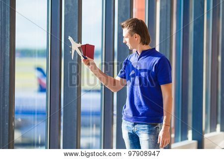 Young man with passports, boarding pass and aircraft toy model at airport