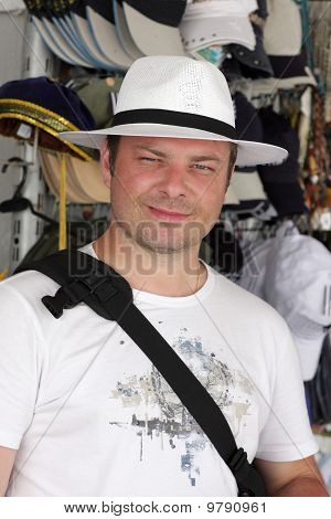 Tourist Poses In Hat Store