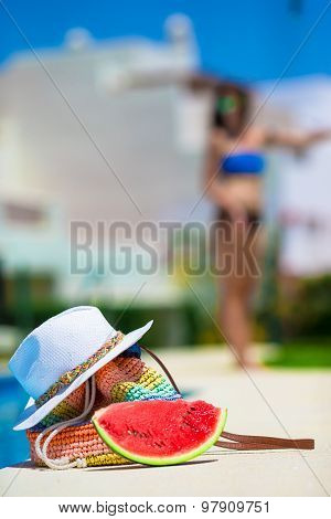 Summer concept- tasty watermelon, straw bag and juice near pool outdoor background young woman