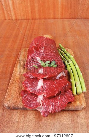 red fresh raw beef veal fillet with asparagus on cutting plate over wooden table prepared to use