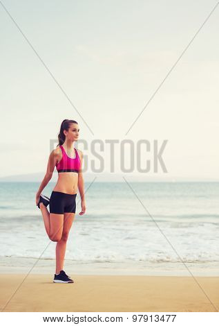 Healthy Active Lifestyle. Young fitness woman stretching and preparing to run on the beach at sunset.