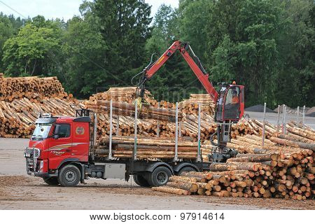 Volvo FH Truck Unloads Logs At Lumber Yard