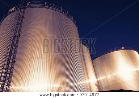 fuel and oil storage towers, tanks at sunset