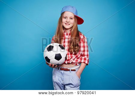 Smiling girl holding soccer ball and looking at camera