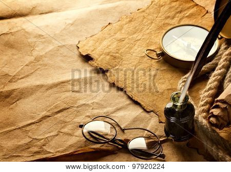 quill pen and vintage spectacles on paper background