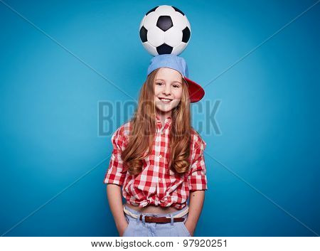 Smiling girl looking at camera with soccer ball on her head