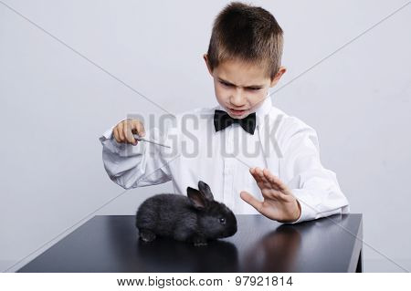 little magician with rabbit studio shot