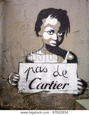 PARIS, FRANCE - MARCH 3RD: Graffiti figure of a poor girl being exploited by the International Company of Cartier. The Slogan Pas De Cartier translates as No to Cartier. On March 3rd 2015