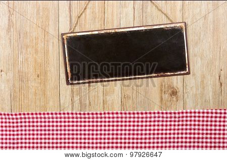 Empty Metal Sign On A Wooden Wall With A Red Checkered Decor