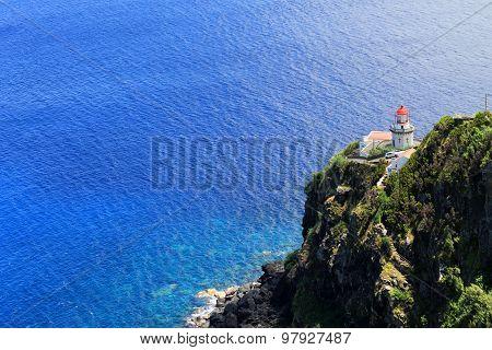 Lighthouse On A Rocky Coast In The Atlantic Ocean