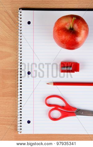 Overhead view of a red pair of scissors, red pencil, sharpener and apple on an open spiral notebook on a wood desk. Back to school concept.