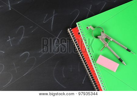 Overhead shot of two spiral bound notebooks with a compass and eraser on a partially erased blackboard. Horizontal format with copy space.